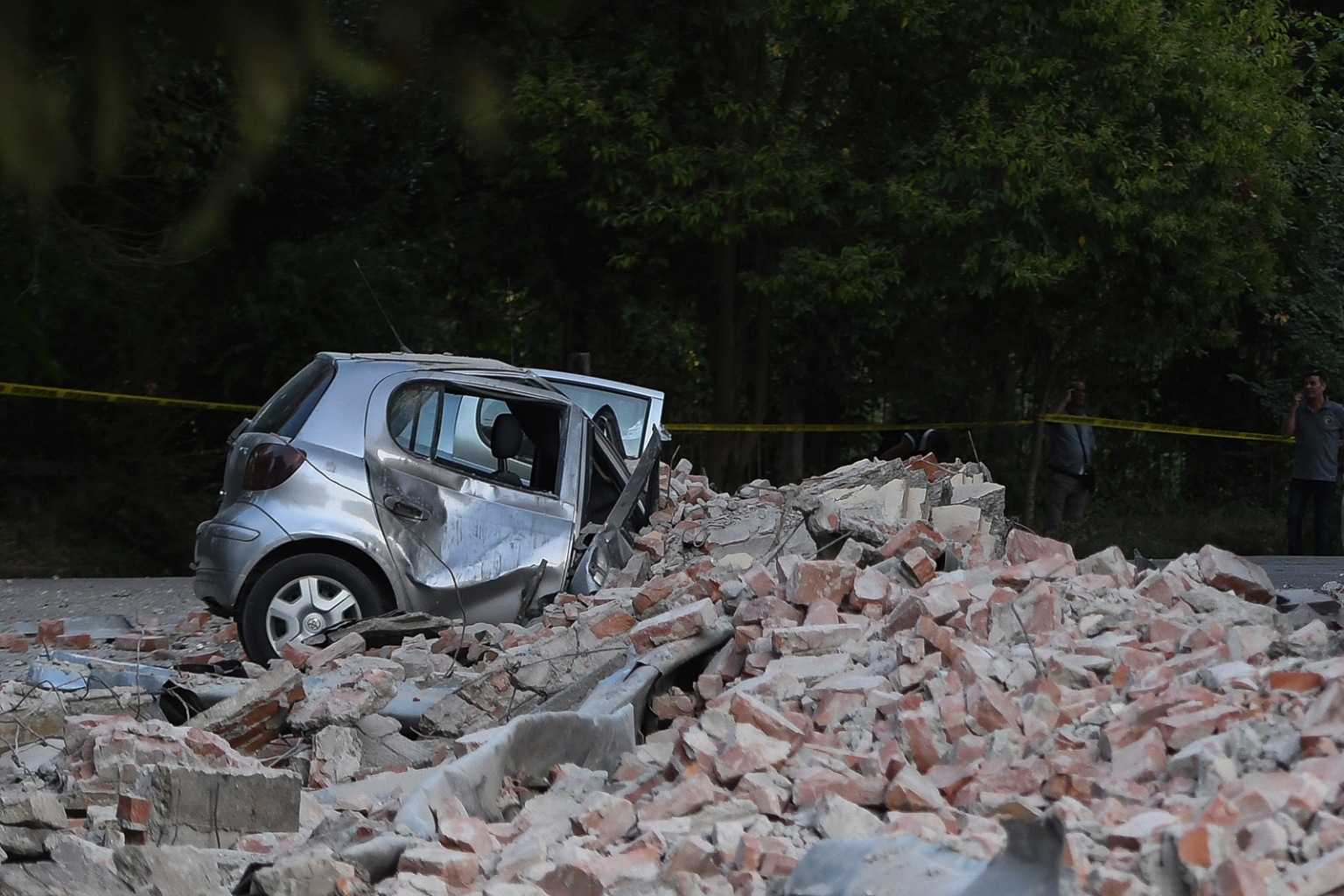 A car is crushed by the partially collapsed roof of a building after two earthquakes over 5.0 magnitude struck the Adriatic coastline of Albania on Sept. 21 GENT SHKULLAKU/AFP/Getty Images
