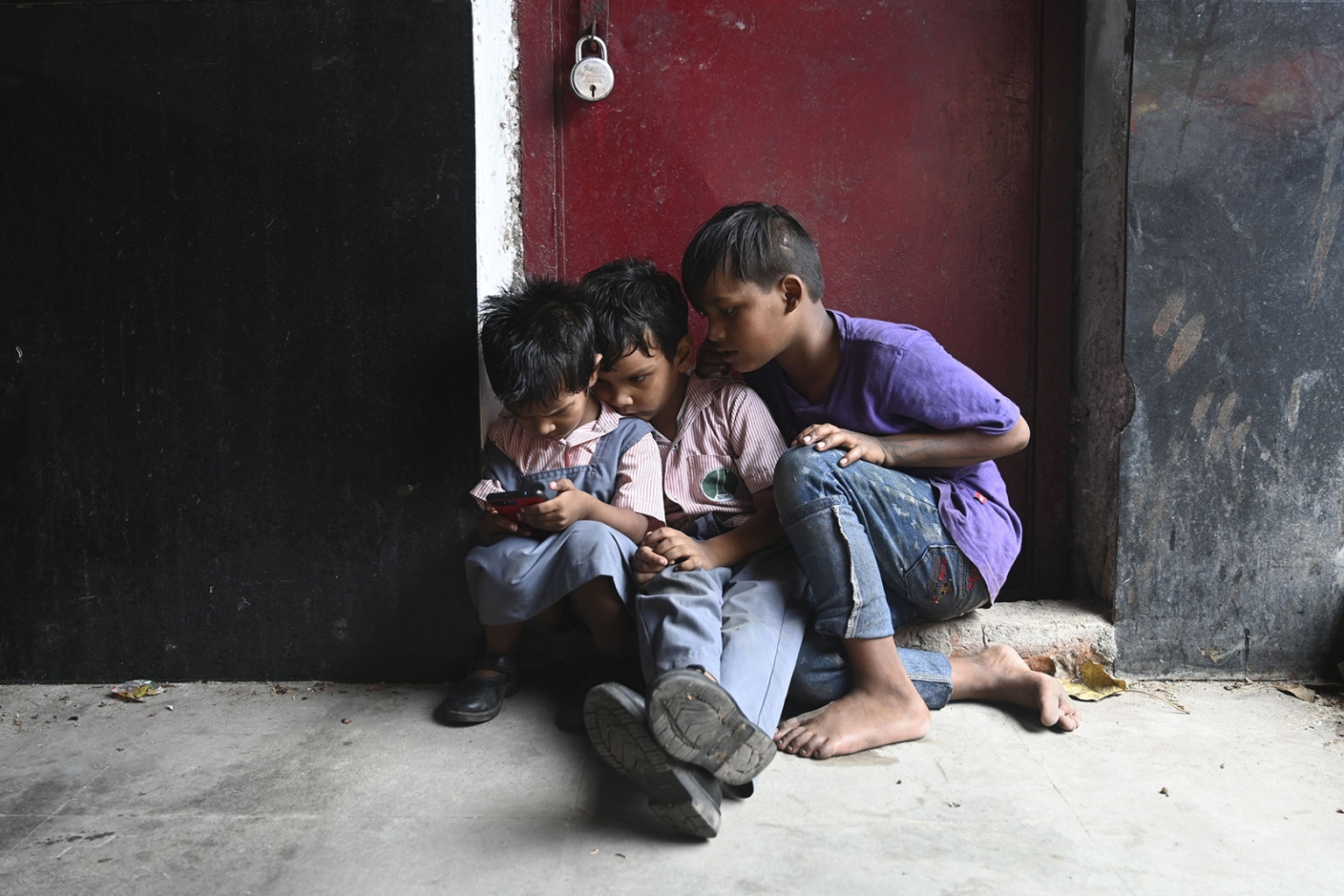 Children play on a cell phone at a market in New Delhi on Sept. 23. SAJJAD HUSSAIN/AFP/Getty Images