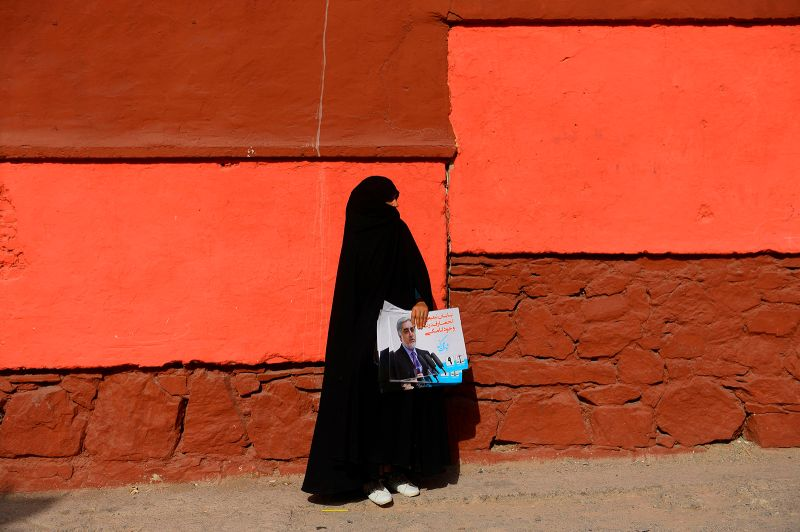 A woman carries posters of presidential candidate Abdullah Abdullah, Afghanistan's current chief executive officer, ahead of the presidential elections in Herat, Afghanistan on Sept. 23. HOSHANG HASHIMI/AFP/Getty Images