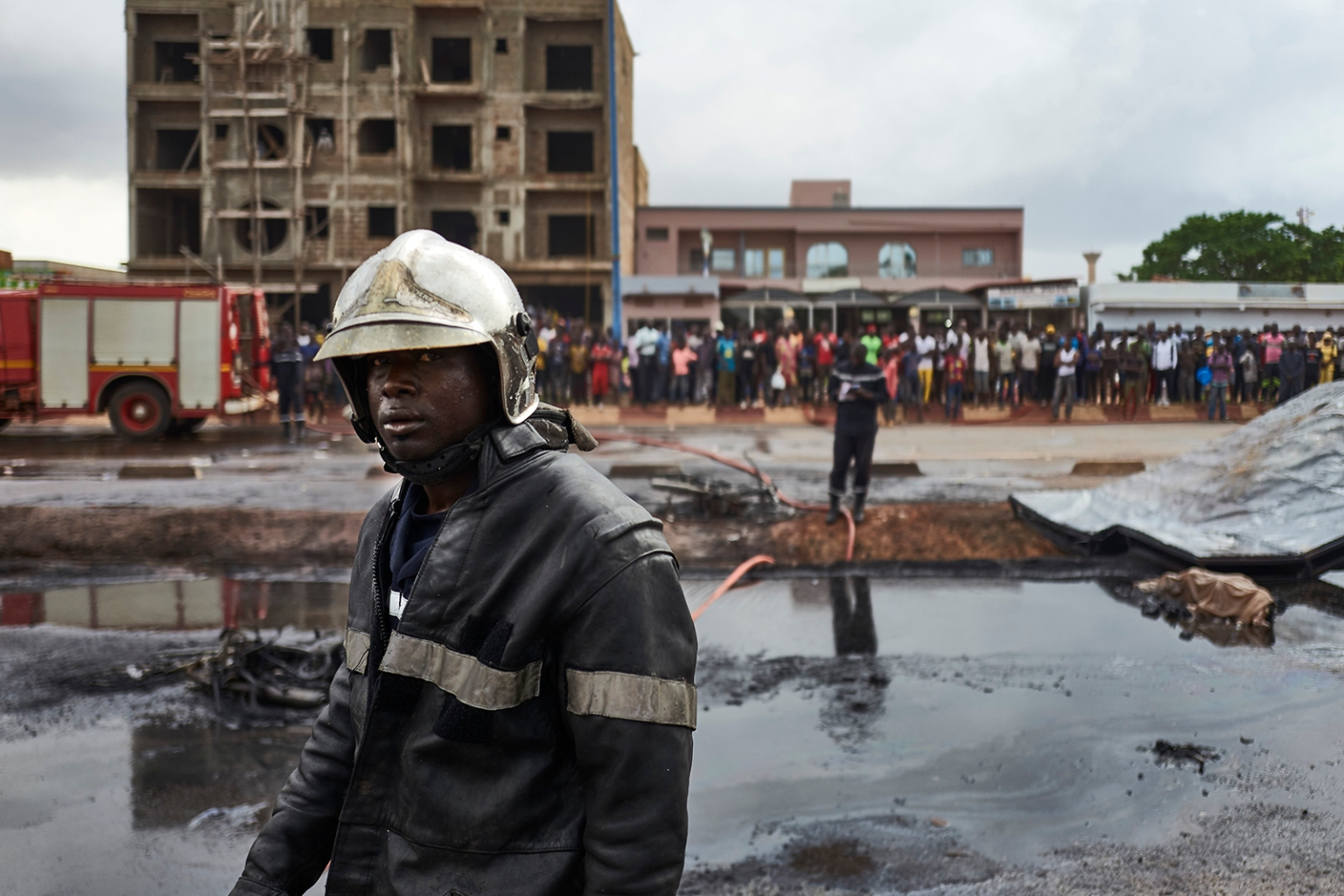 A firefighter stands at the scene of a car accident involving a fuel tank truck that caught fire when people tried to lift it, killing at least five people and injuring 15, in central Bamako, Mali, on Sept. 24. MICHELE CATTANI/AFP/Getty Images