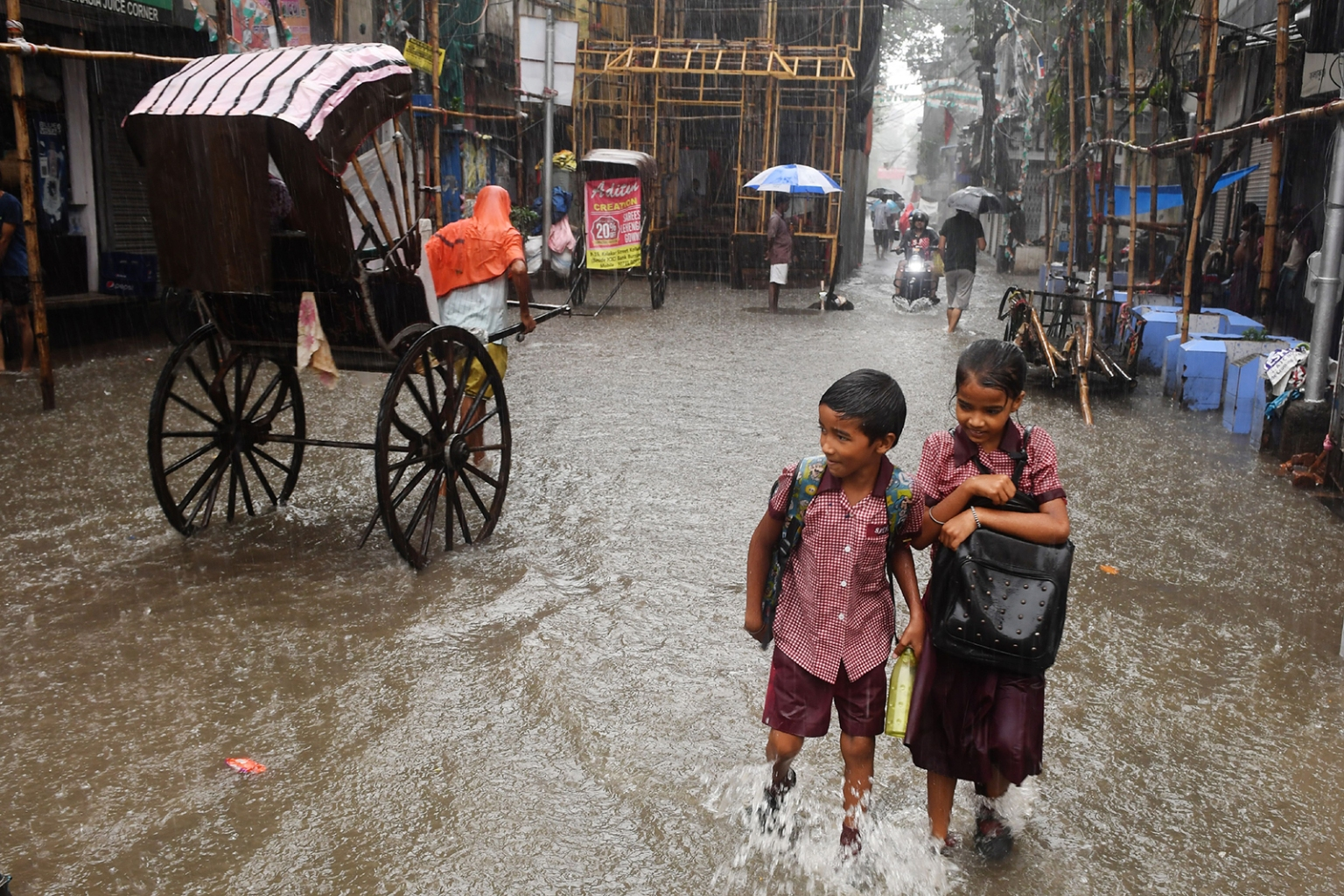 Indian schoolchildren walk through a waterlogged road during heavy rain in Kolkata on Sept. 25. DIBYANGSHU SARKAR/AFP/Getty Images