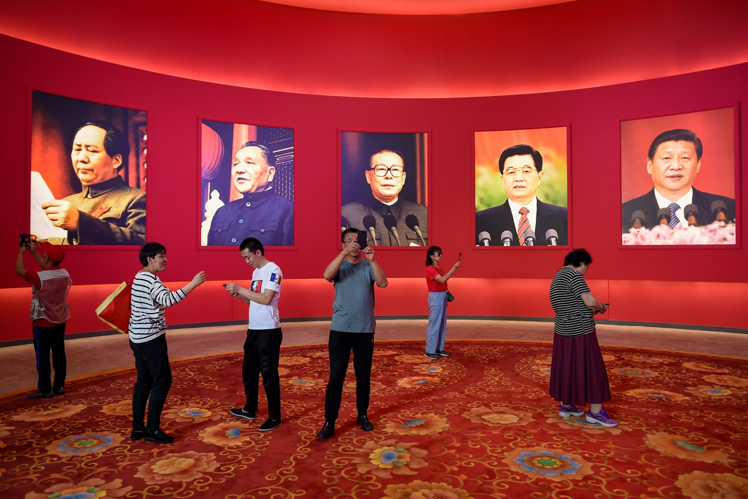 People take pictures in front of portraits of past and present Chinese leaders at an exhibition marking the country's achievements over the past 70 years ahead of the 70th anniversary of the founding of the People's Republic of China in Beijing on Sept. 26. WANG ZHAO/AFP/Getty Images