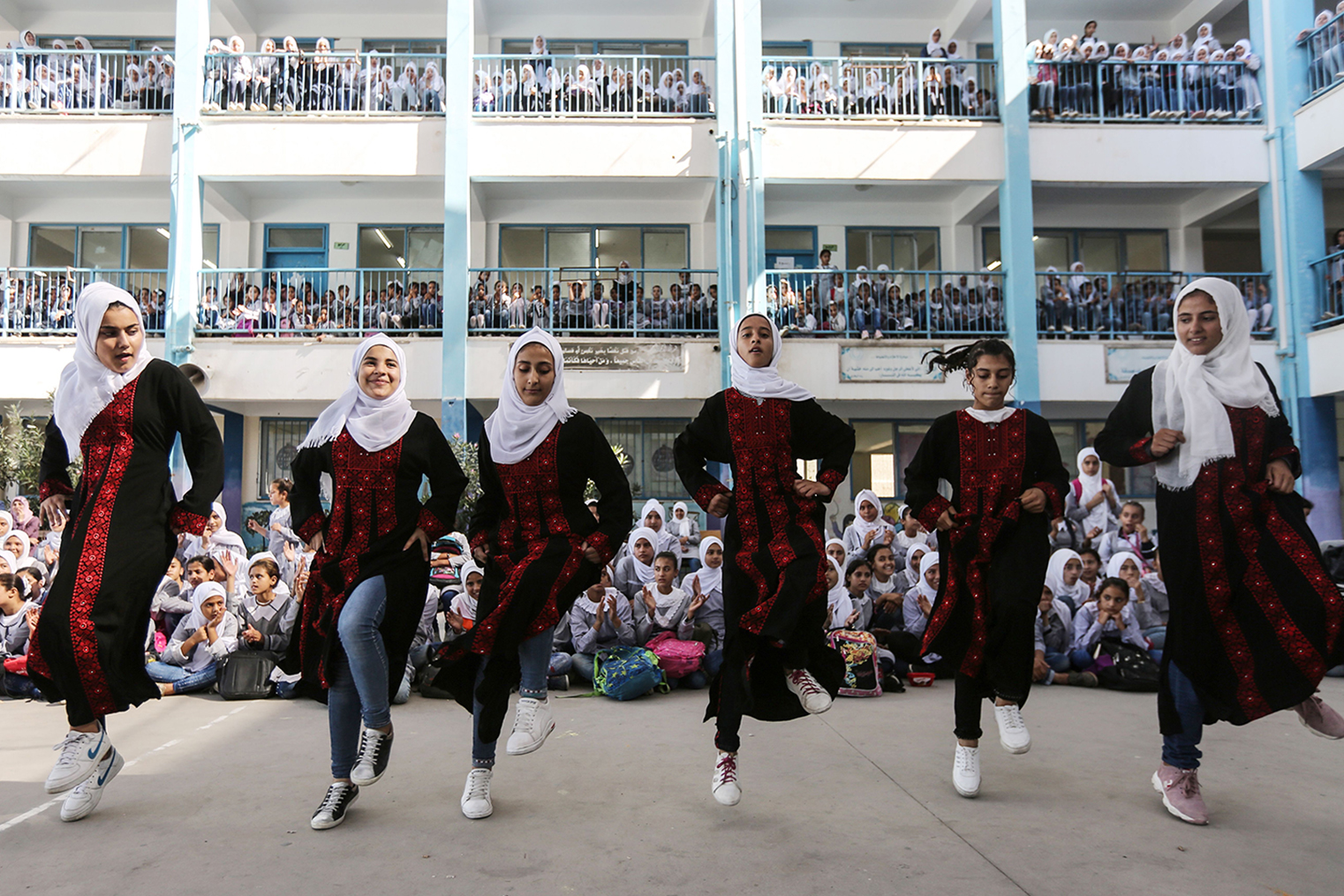 Palestinian schoolgirls in national dress take part in a traditional dance as musicians from the Edward Said National Conservatory of Music perform at a United Nations Relief and Works Agency school in Beit Hanoun, in the Southern Gaza Strip, on Sept. 26. MAHMUD HAMS/AFP/Getty Images