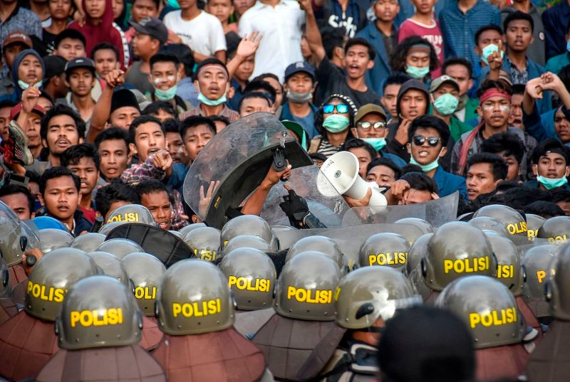 Indonesian riot police charge toward protesters during a demonstration in Mataram on Sept. 30.