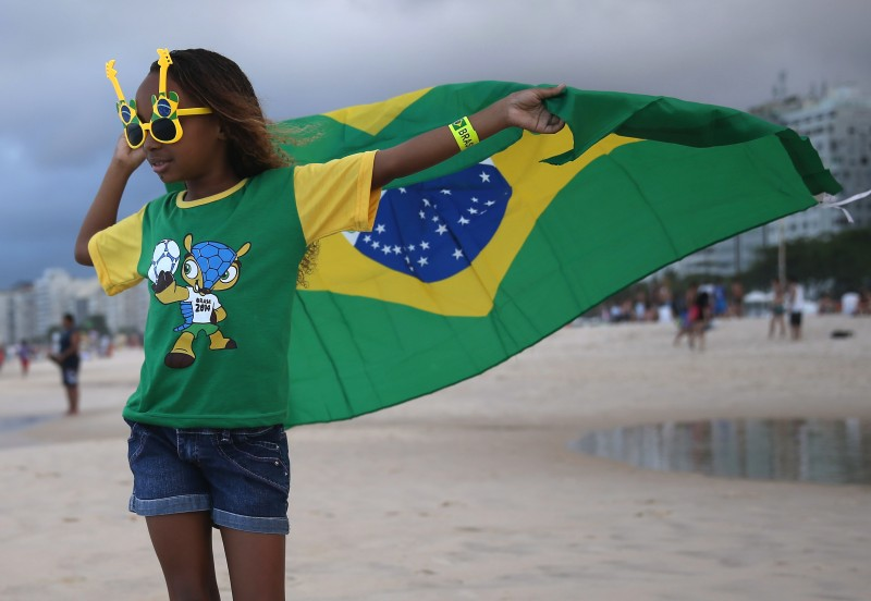 Brazilian soccer team fan, Giovanna Selena, from Brazil, flies her countries flag as she enjoys Copacabana beach while waiting for the start of the 2014 FIFA World Cup on June 11, 2014 in Rio de Janeiro, Brazil.