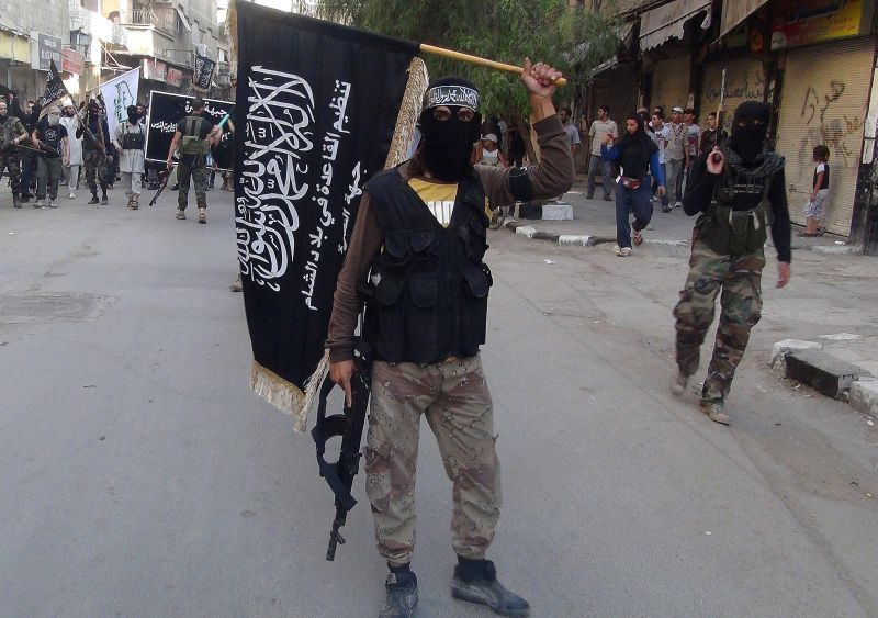 Islamic fighters from the al-Qaida group in the Levant, Al-Nusra Front, wave their movement's flag as they parade at the Yarmuk Palestinian refugee camp, south of Damascus, to denounce Israels military offensive on the Gaza Strip, on July 28, 2014.