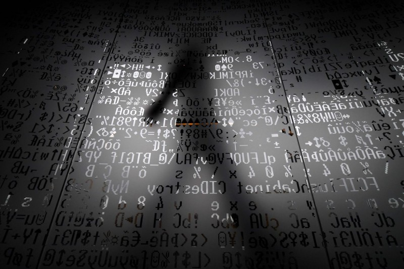 An employee walks behind a glass wall with machine coding symbols at the headquarters of the internet security giant Kaspersky in Moscow on Oct. 17, 2016.