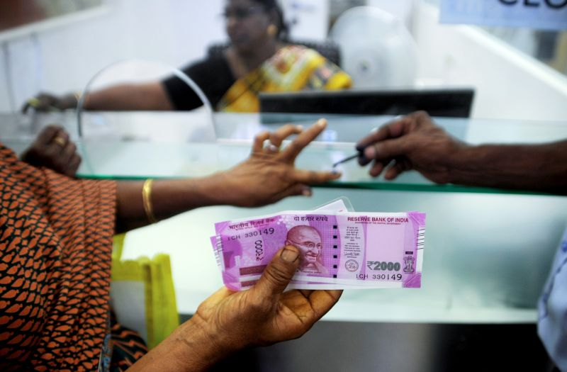 An Indian woman displays her 2000 rupee notes as she has her finger inked with indelible ink after exchanging withdrawn 500 and 1000 rupee banknotes at a bank in Chennai on November 17, 2016.