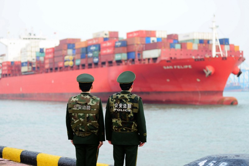 Chinese police officers watch a cargo ship at a port in Qingdao, in China's eastern Shandong province, on March 8, 2018.
