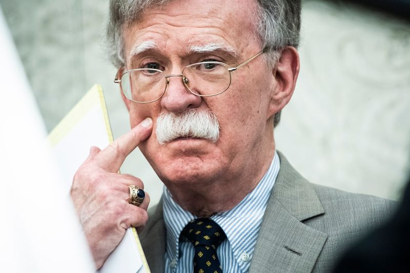 U.S. National Security Advisor John Bolton listens to President Donald Trump in the Oval Office at the White House on Aug. 20.