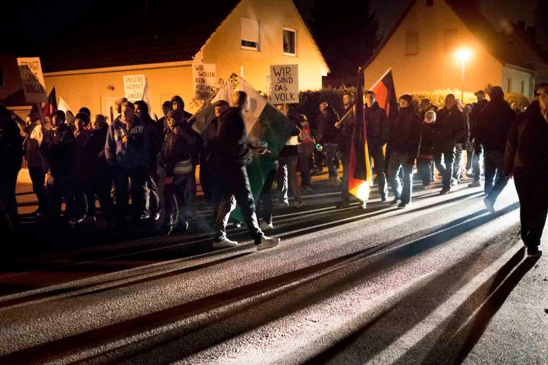 "Far-right activists carrying German and Saxon flags and chanting ""Wir sind das Volk"" (We are the people) cast shadows as they gather to protest against a planned refugee center on Nov. 14, 2013 in Roetha, Germany."