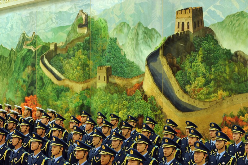 Chinese People's Liberation Army honor guards stand in front of a mural of the Great Wall inside the Great Hall of the People in Beijing on Nov. 9, 2010.
