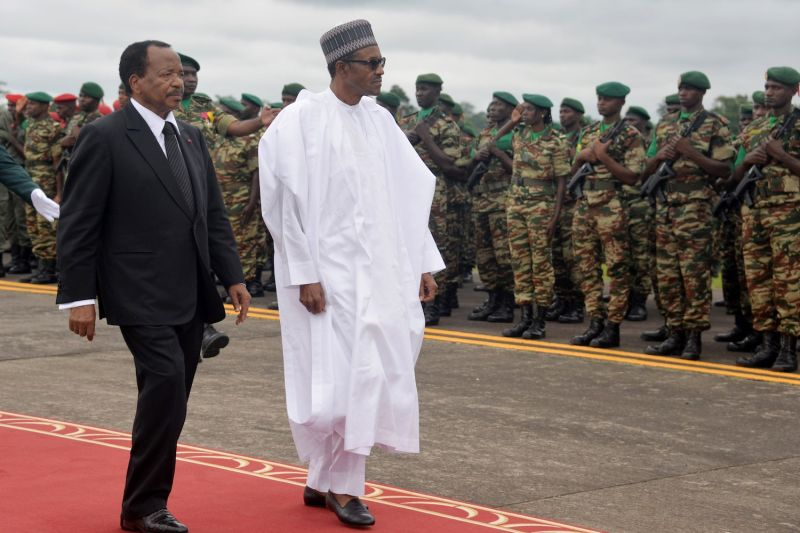President of Cameroon Paul Biya (L) walks with Nigerian President Muhammadu Buhari (R) following his arrival at the airport in Yaoundé, Cameroon, on July 29, 2015.