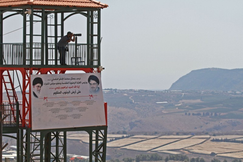 "A man uses binoculars to view the border with Israel on Sept. 2 at the ""Garden of Iran"" Park, which was built by the Iranian government, in the southern Lebanese village of Maroun al-Ras."