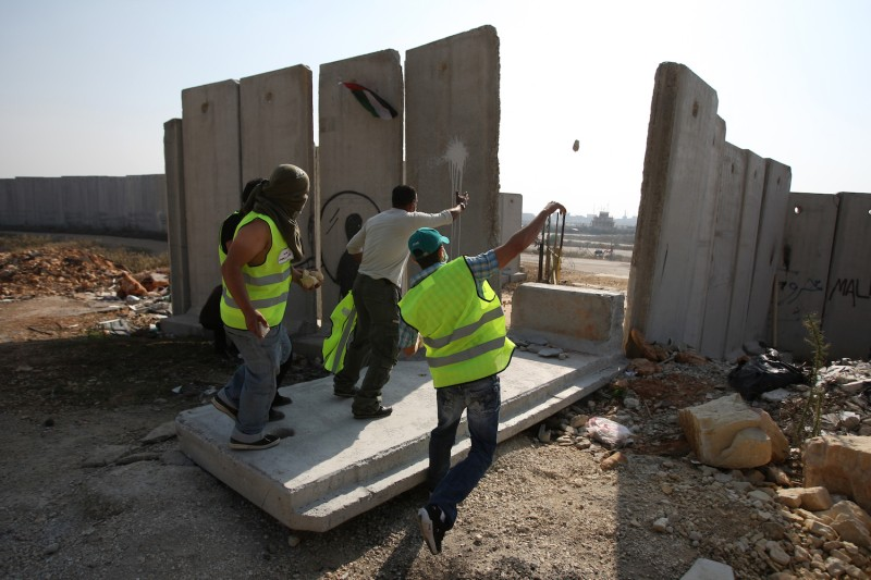 Local and international peace activists stand on a concrete block, part of Israel's controversial separation barrier, after pulling it down during a protest near the West Bank city of Ramallah, on Nov. 9, 2009 to mark the 20th anniversary of the fall of the Berlin Wall in Germany.