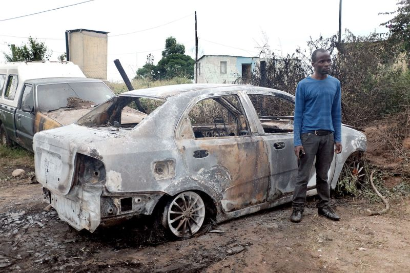 A Zimbabwean man stands by one of his two cars that was set on fire after he survived a petrol bomb attack at his home near Durban, South Africa on April 19, 2015.
