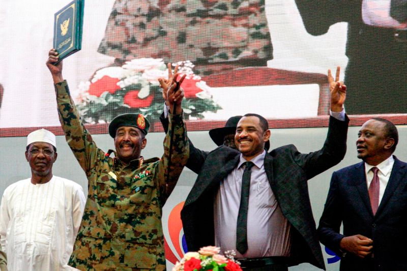 Sudan's protest leader Ahmad Rabie (C-R), flashes the victory gesture alongside General Abdel Fattah al-Burhan (C-L), the chief of Sudan's ruling Transitional Military Council, during a ceremony where they signed a constitutional declaration that paves the way for a transition to civilian rule, in Khartoum on Aug. 17.
