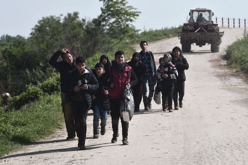 Syria refugees walk after they crossed the Evros river, the natural boundary with Turkey in northeastern Greece, in the village of Pythio, on April 28, 2018.