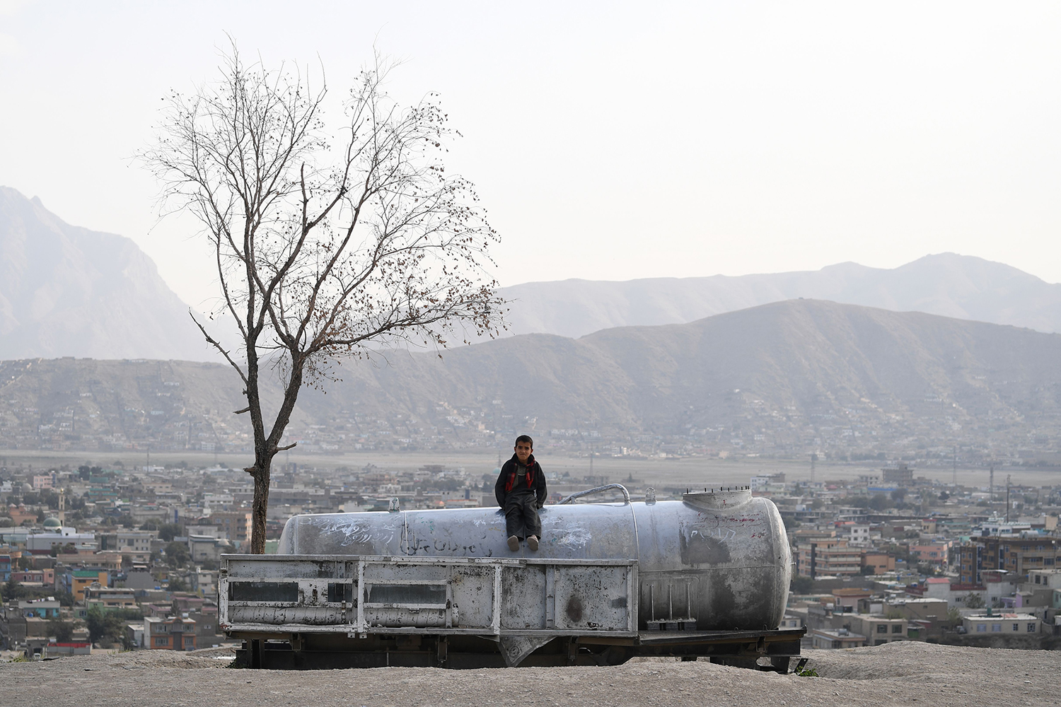 An Afghan child sits on a water tank at Nadir Khan hill in Kabul on Oct. 1. SAJJAD HUSSAIN/AFP/Getty Images