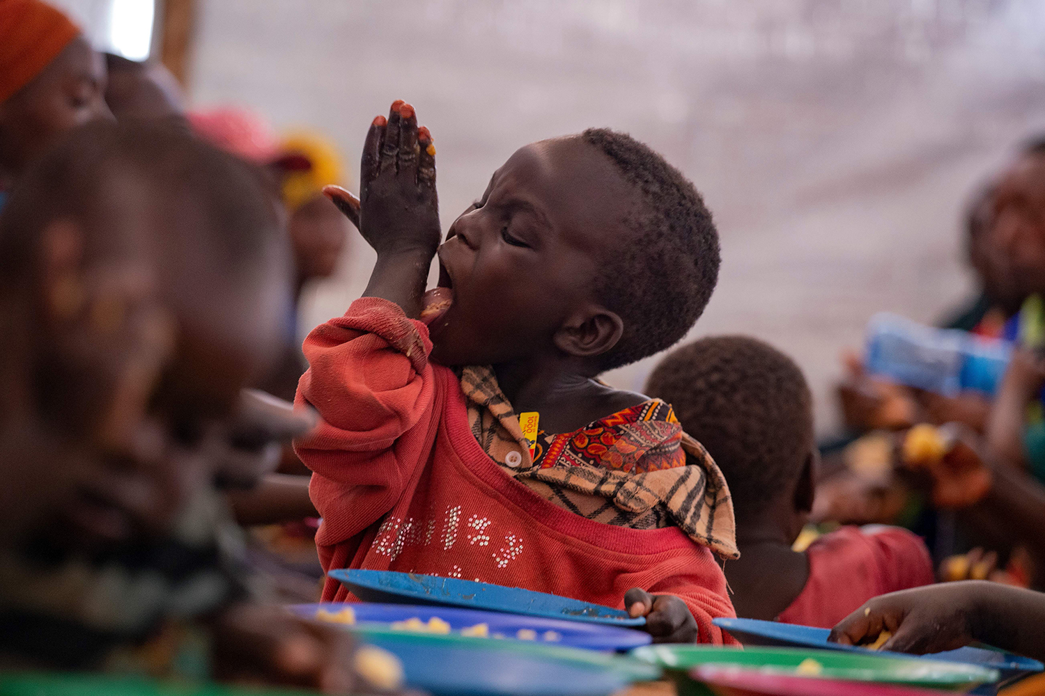A young Burundian refugee licks his hand during a meal at the Nyabitara Transit site in Ruyigi, Burundi, on Oct. 3.  Nearly 600 Burundians who fled political violence in their home country to Tanzania were repatriated voluntarily, the U.N. refugee agency said, after the Tanzanian government vowed that from Oct. 1 it would start repatriating all Burundians, willing or not. TCHANDROU NITANGA/AFP via Getty Images