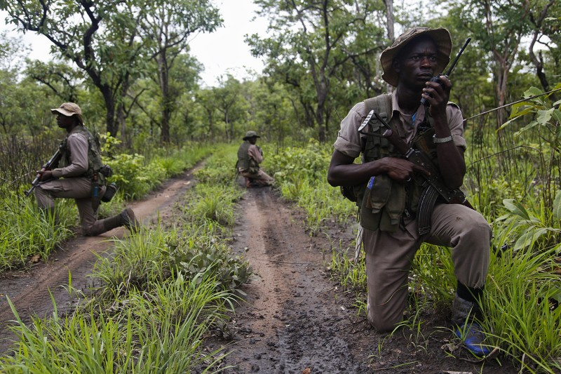 Jean Ghodjendji radios back to colleagues at an advance post during a foot patrol in Bamingui-Bangoran National Park in the Central African Republic while fellow rangers scan the forest on May 18.