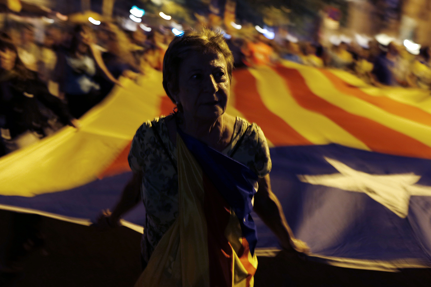 A demonstrator pulls a giant Catalan pro-independence flag during a protest marking the second anniversary of a banned independence referendum in Barcelona on Oct. 1. PAU BARRENA/AFP via Getty Images