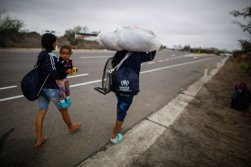 Venezuelan migrants walk along the border of Peru and Ecuador.