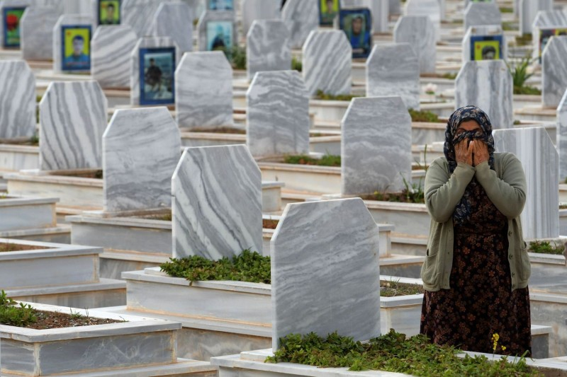 Relatives visit the tombs of Syrian Democratic Forces fighters in the northern Syrian Kurdish town of Kobani.