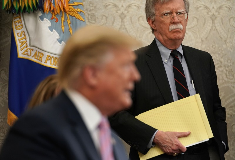 National Security Advisor John Bolton listens to U.S. President Donald Trump speak during a meeting with Egyptian President Abdel-Fattah el-Sisi in the Oval Office of the White House on April 9.