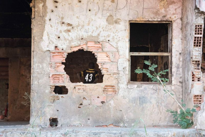 A boy living in a derelict building damaged during the Angolan civil war is seen through a hole in Kuito, in Angola's Bie province, on June 2.