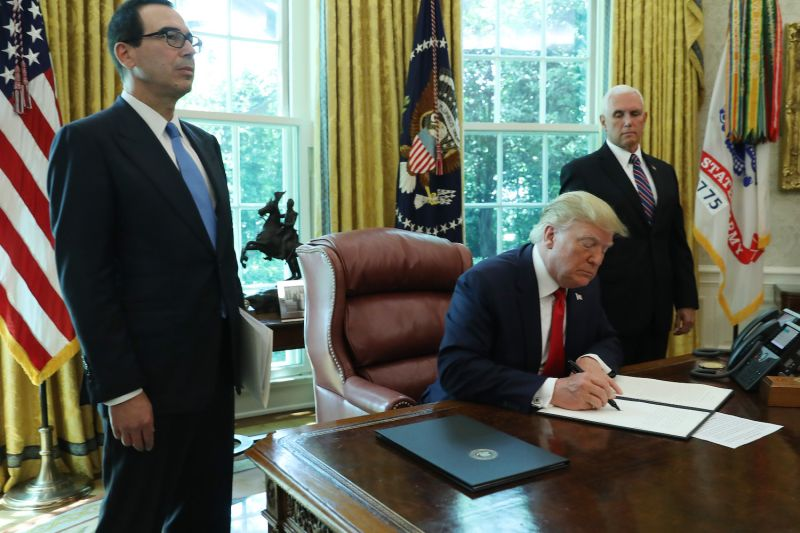 U.S. President Donald Trump signs an executive order imposing new sanctions on Iran as Vice President Mike Pence, right, and Treasury Secretary Steven Mnuchin look on, in the White House on June 24.
