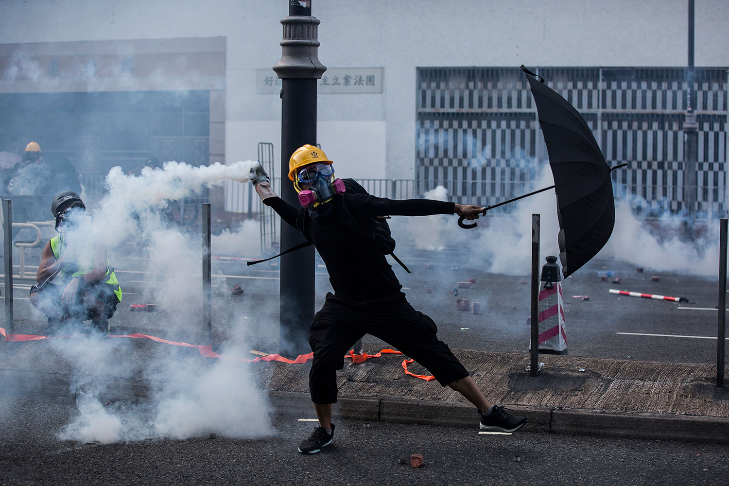 A protester throws a tear gas canister fired by police in the Sha Tin district of Hong Kong on Oct. 1. ISAAC LAWRENCE/AFP/Getty Images