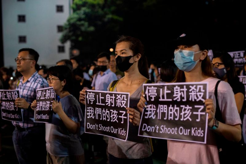 "People hold signs reading ""Don't shoot our kids"" as they gather in the Tsuen Wan area of Hong Kong on Oct. 2."