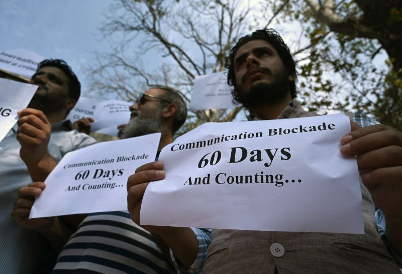 Protesters hold signs against the ongoing restrictions of the internet and mobile phone networks at the Kashmir Press Club in Srinagar on Oct. 3.