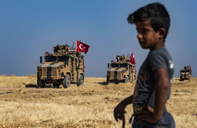 A Syrian boy watches as Turkish military vehicles, part of a U.S. military convoy, take part in joint patrol in the Syrian village of Hashisha on the outskirts of Tell Abyad town along the border with Turkey on Oct. 4.
