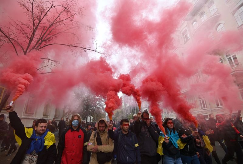 Demonstrators hold smoke grenades as they gather in Kyiv, Ukraine.
