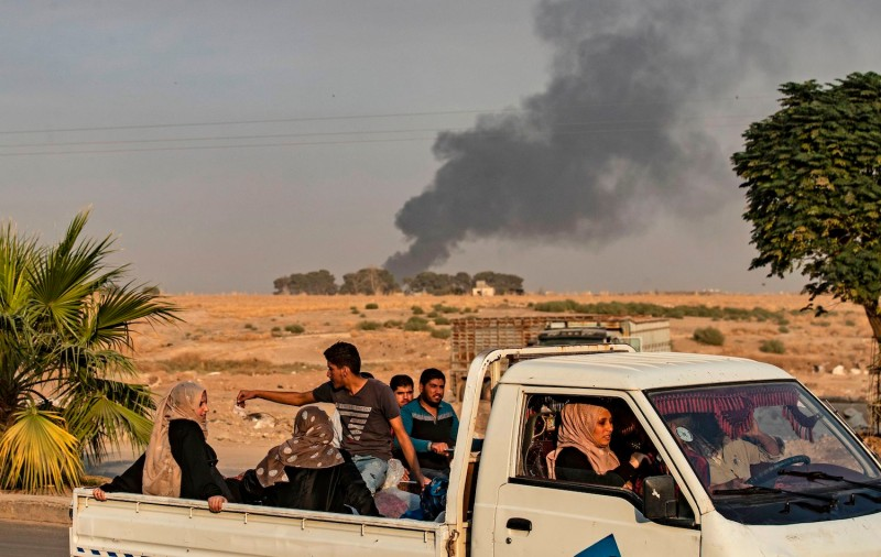 Syrians drive past a town in northeastern Syria following a Turkish bombardment.