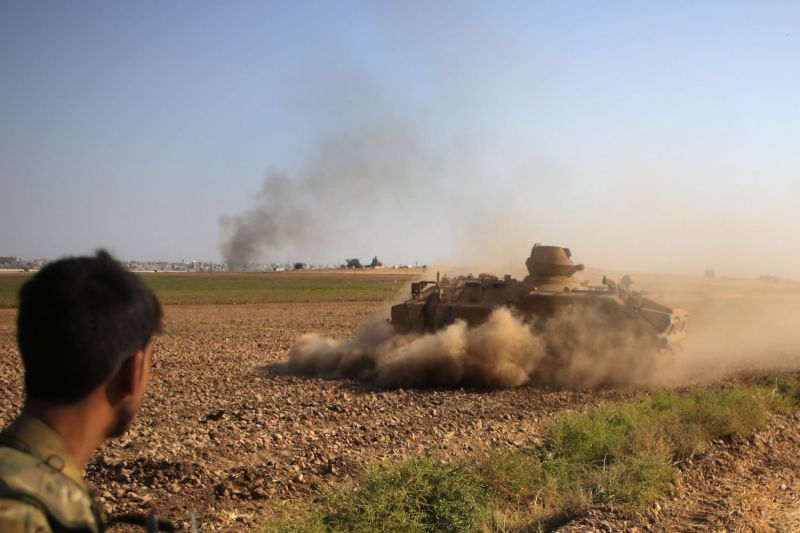 A Syrian fighter with Turkish-backed forces watches an armored personnel carrier maneuvering on the outskirts of the Syrian border town of Tal Abyad on Oct. 13, 2019.