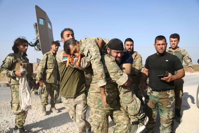 Turkish-backed Syrian fighters evacuate a wounded comrade near the Syrian border.
