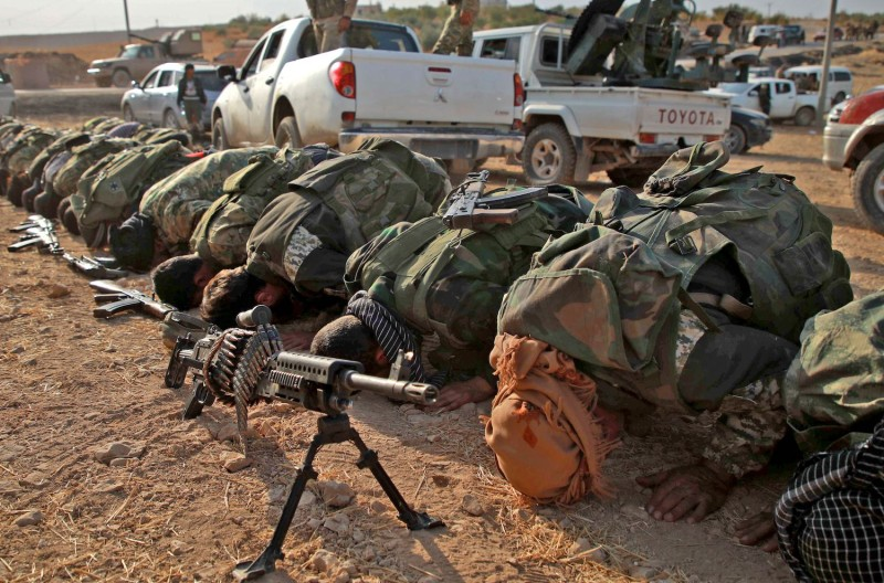 Turkish-backed Syrian fighters kneel to pray.