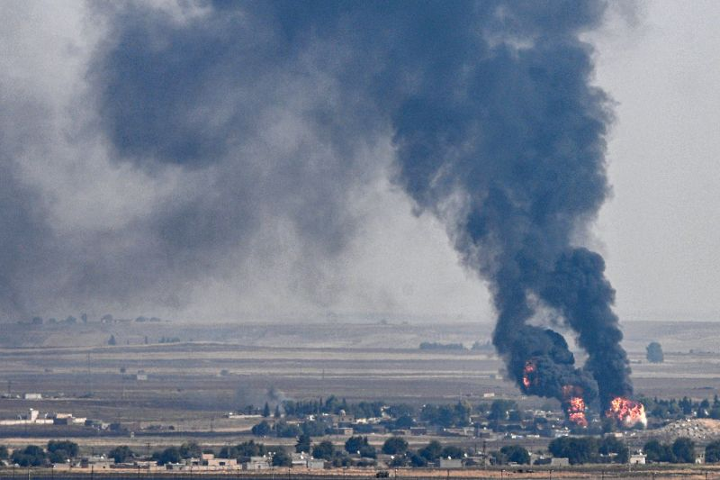 This picture taken on October 17, 2019 from the Turkish side of the border with Syria in the Ceylanpinar district city of Sanliurfa shows smoke and fire rising from the Syrian town of Ras al-Ain during the Turkish offensive against Kurdish groups in northeastern Syria.