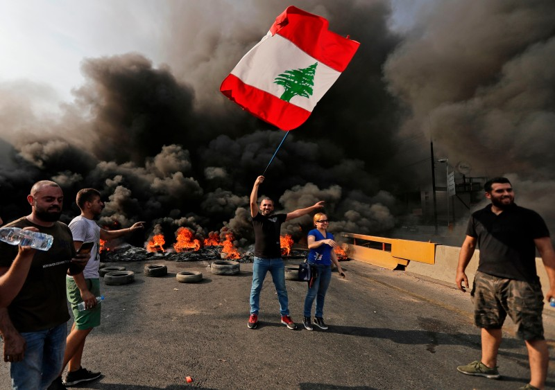 Lebanese demonstrators burn tires and wave their national flag during a protest against dire economic conditions on a highway between Beirut and the northern city of Tripoli on Oct. 18.