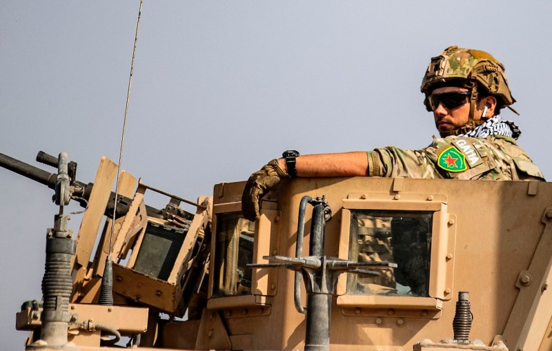 A soldier wearing a Kurdish Women's Protection Units badge sits on top of a U.S. military vehicle on a road in the town of Tal Tamr, Syria, on Oct. 20.