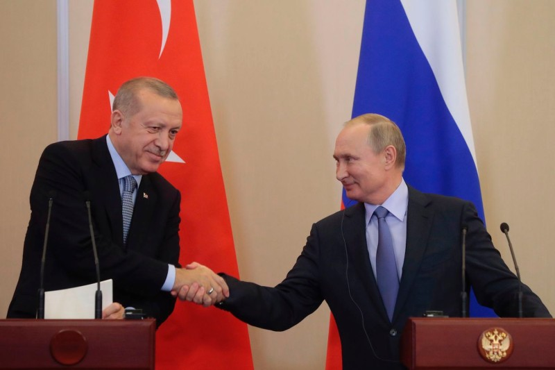 Presidents Vladimir Putin and Recep Tayyip Erdogan shake hands.