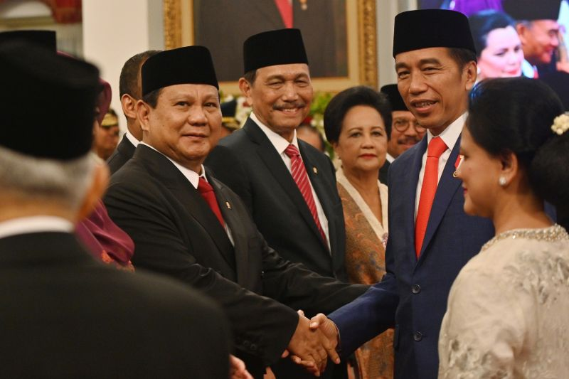 Indonesian President Joko Widodo shakes hands with Defense Minister Prabowo Subianto