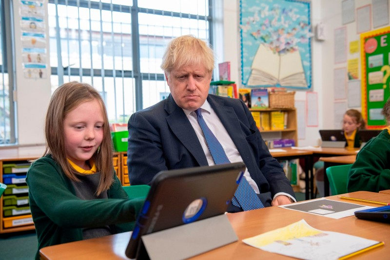 British Prime Minister Boris Johnson sits with pupils as he visits Middleton Primary School in Milton Keynes, England, on Oct. 25.