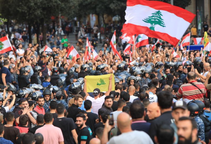 Lebanese security forces stand between supporters of the Shiite Hezbollah movement (foreground) and anti-government protesters (background) at Riad al-Solh Square in Beirut on Oct. 25.