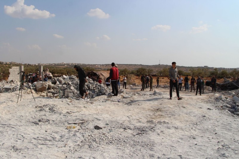 "Syrians gather amid the rubble of a building at the site of helicopter gunfire which reportedly killed nine people near the northwestern Syrian village of Barisha in Idlib province along the border with Turkey, where ""groups linked to the Islamic State  group"" were present, according to a Britain-based war monitor with sources inside Syria, on Oct. 27."