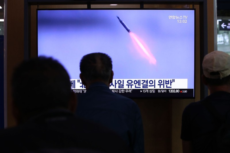 People watch a TV showing a file image of a North Korean missile launch at the Seoul Station in Seoul on Oct. 2.