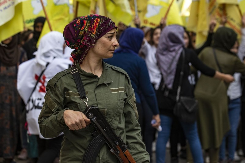 A member of the Kurdish internal security services known as Asayish stands guard during a demonstration by Syrian Kurds against the Turkish assault on northeastern Syria and in support of the Syrian Democratic Forces, in Syria's northeastern city of Qamishli on Oct. 28, 2019.